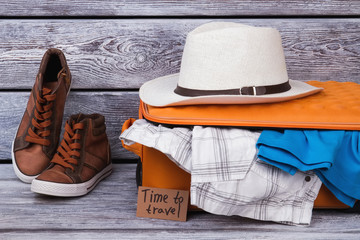 Set of men's clothing and accessories. Travel concept, packed suitcase, wooden background.