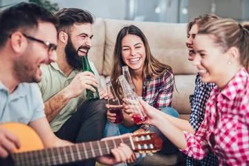 Group of happy young friends having fun and drinking beer in home interior