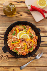 Spanish paella in a frying pan on a wooden background