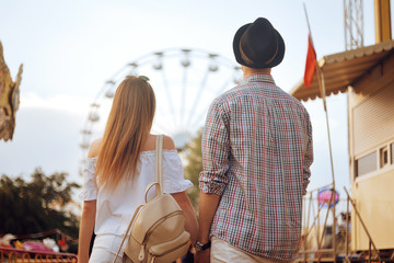 Beautiful, young couple having fun at an amusement park. Couple Dating Relaxation Love Theme Park Concept. Couple posing together on the background of a ferris wheel. Tourists have fun, smile