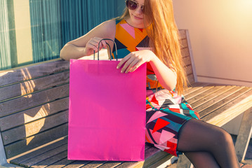 Young woman sitting and looking into shopping bag