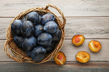 Ripe and sweet plums in basket on wooden table