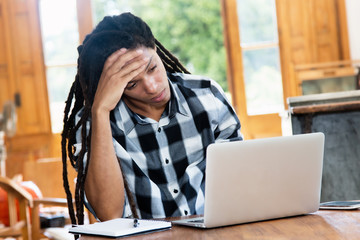 Thinking latin american man with dreadlocks at computer