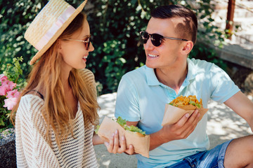 Beautiful young couple eating hot dog, spending time with pleasure, outdoors. Dressed in casual clothes, in sunglasses. Summertime.