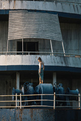 Photoshoot of a young beautiful mixed race woman on a huge abandoned ship in the Asian jungle.