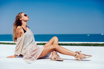 Profile of a gorgeous model in sunglasses, wearing stylish clothes, sitting on bench, against the sea background. Summertime.