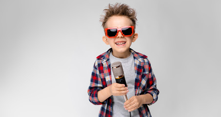 A handsome boy in a plaid shirt, gray shirt and jeans stands on a gray background. A boy wearing sunglasses. The red-haired boy wound the wire around his arm. The boy holds a microphone in his hand