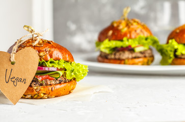 Vegan bean burgers with vegetables and tomato sauce on white dish, copy space. Healthy vegan food concept.