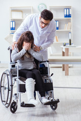 Male doctor examining female patient on wheelchair