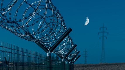 Close-up of sharp razor wire on fence. Gloomy blue sky and moon in background. Abstract industrial or military compound with barbed tape in a field with power line. Illuminated by artificial lighting.