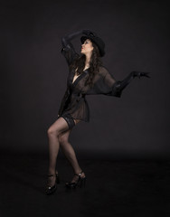 Beautiful young girl dancing in black tunic, black gloves and black hat.