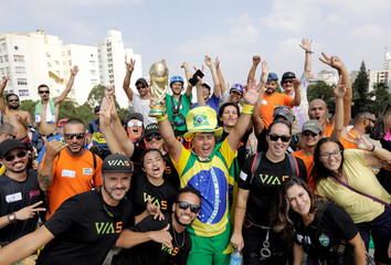 Brazilian climbers react before they go for the world record of largest rappel mosaic forming the Brazilian flag and an image of the World Cup trophy at Sumare bridge in Sao Paulo