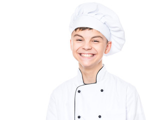 Handsome teen boy wearing chef uniform. Portrait of a happy cute male child cook, isolated on white background. Food and cooking concept.