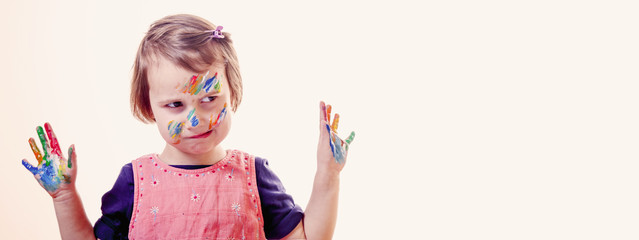 Funny facial expression of little cute girl with children's makeup and painting colorful hands.