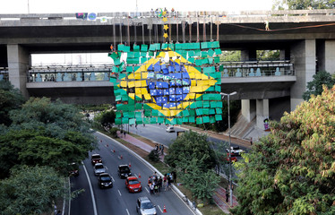 Brazilian climbers attempt the world record of largest rappel mosaic as they form the Brazilian flag with an image of the World Cup trophy at Sumare bridge in Sao Paulo