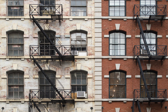 Close-up view of New York City style apartment buildings with emergency stairs along Mott Street in the Chinatown neighborhood of Manhattan NYC.