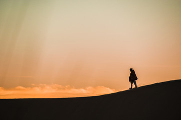 Man walk on a desert sand dunes at sunset in Rajasthan, India.
