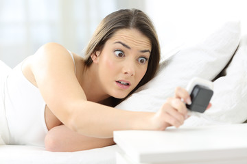 Worried woman checking alarm waking up late