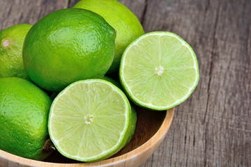Fresh lime in a bamboo bowl on wood table