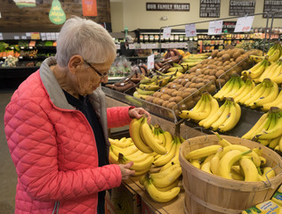 An Elderly Woman Shopping for Bananas in the produce section of the supermarket.  She is wearing a bright pink jacket.