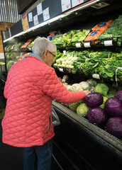 An Elderly Woman Shopping for Cabbage in the produce section of the supermarket.  She is wearing a bright pink jacket.