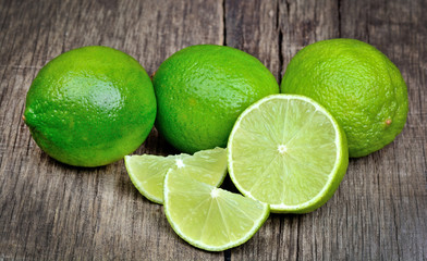 Lime slice and green limes on wooden background