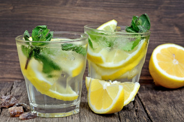 Detox water with lemons and mint on old table