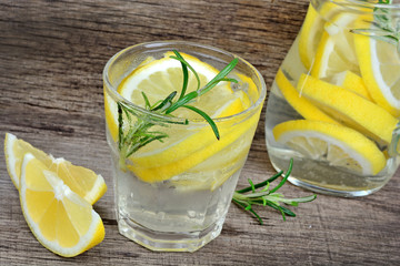 Lemon and rosemary detox water in a glass on wood table.  Refreshing cold summer drink