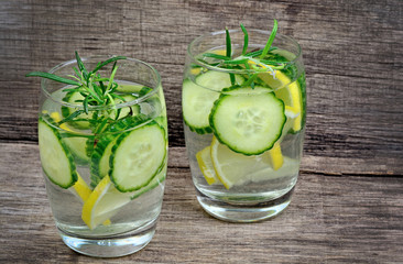 Fresh cold water with lemon, cucumber and rosemary in a glasses