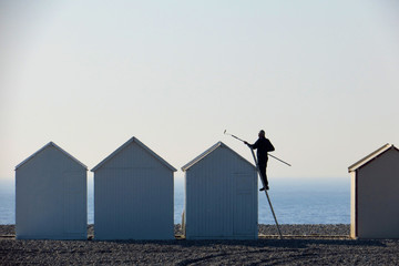 A man paints the roof of a beach cabin on a pebbled beach in Cayeux-sur-Mer