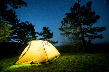 Glowing camping tent in the night mountain forest under a starry sky