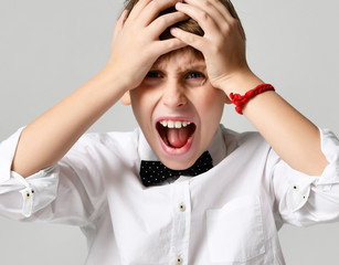 Young school boy screaming and crying close up on gray