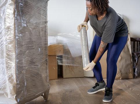 Black woman moving furniture