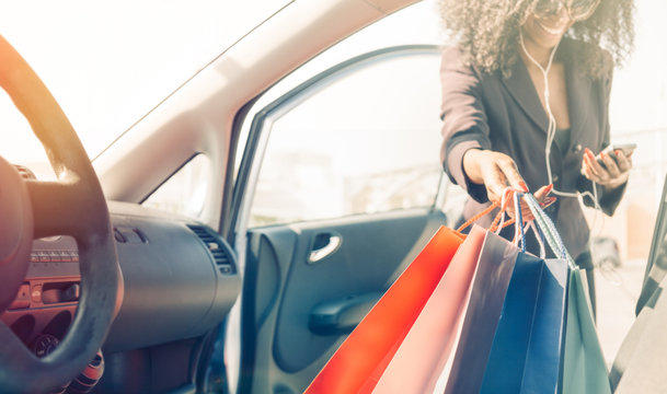 black girl with shopping bags entering in car while  using smart phone