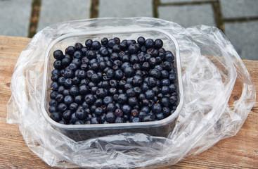 Plastic basin full of blueberries.