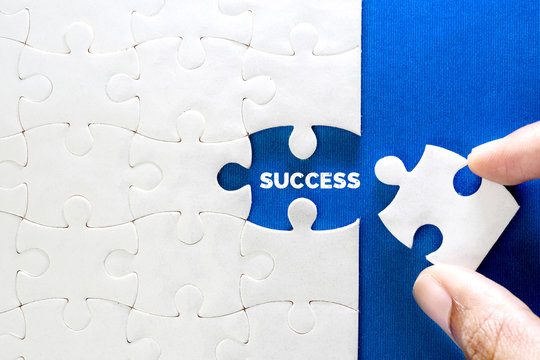 Close up piece of white jigsaw puzzle with SUCCESS text , a concept of business challenge success completion with teamwork