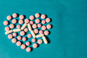 on a blue background of tablets and pills lined with heart shape with a cardiogram. The concept of a cure for the heart