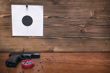 Gun pistol and paper target. Shooting practice. Shooting range background with copy space.