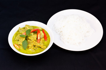 Thai food.Green curry with pork and rice noodles on black background.