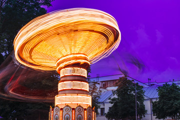 Blurred Motion Effect Of Illuminated Rotating Carousel Merry-Go-Round. Summer