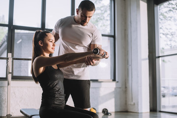 male personal trainer helping sportswoman to do exercises with dumbbells at gym