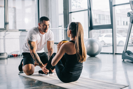 male personal trainer helping sportswoman to do abs with ball at gym