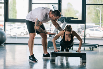 male personal trainer helping sportswoman to do push ups at gym