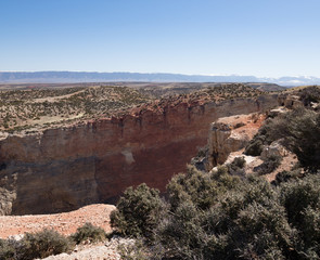 The Canyon Wall at Bighorn Canyon National Recreation Area with shrubs on the foreground and cloudless blue sky above.