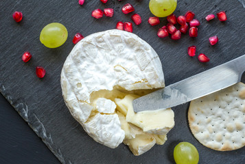 Camembert cheese, knife, cracker and pomegranate seeds on cheese slate board