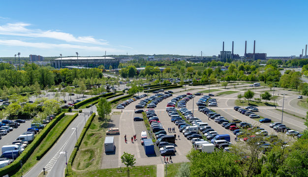 Aerial view over a large parking lot with many parked cars onto a football stadium and the factory