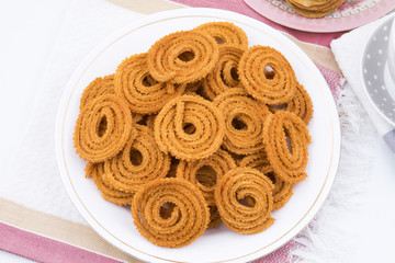 Indian Traditional Snack Chakli, a spiral shaped crisp deep fried snack, It is known as  Chakali, Murukku, Muruku, Murkoo, Chakri in Gujarat, Chakli in Maharashtra and Northern India