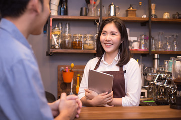 Female barista talking with customer at cafe. Barista working with happy emotion. People working concept.