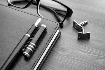 Business accessories on desktop: notebook, diary, fountain pen, glasses.