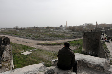 A man watches Sur neighbourhood, ravaged by urban warfare between security forces and Kurdish militants and then flattened by diggers, as he sits on top of UNESCO World Heritage Roman-era city walls in Diyarbakir